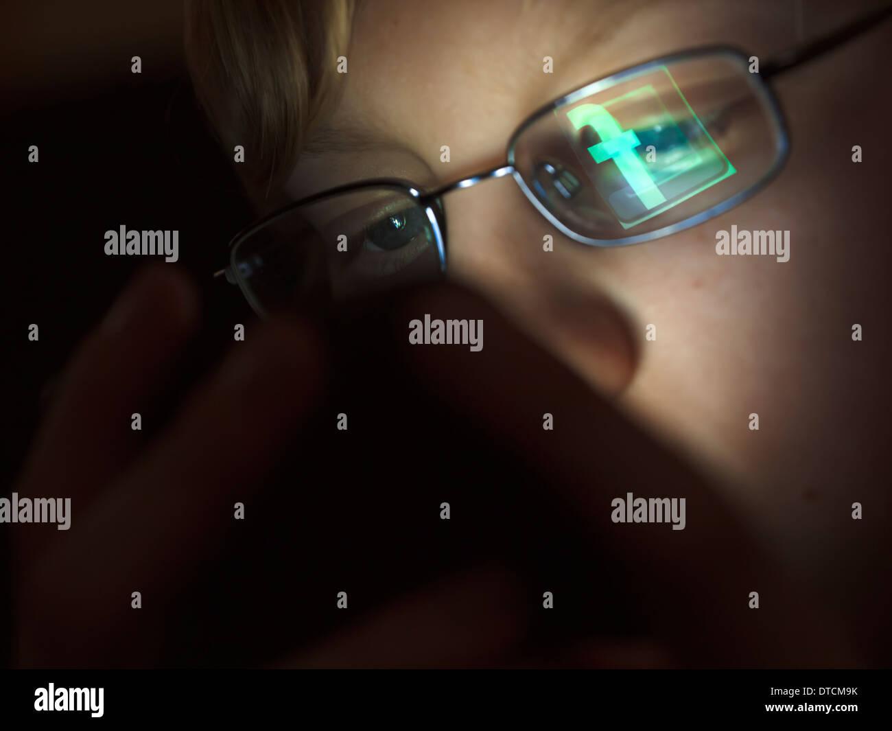 Un ragazzo adolescente è di navigare su internet usando il suo iPhone con il logo di Facebook si riflette nel ragazzo in bicchieri. Immagini Stock