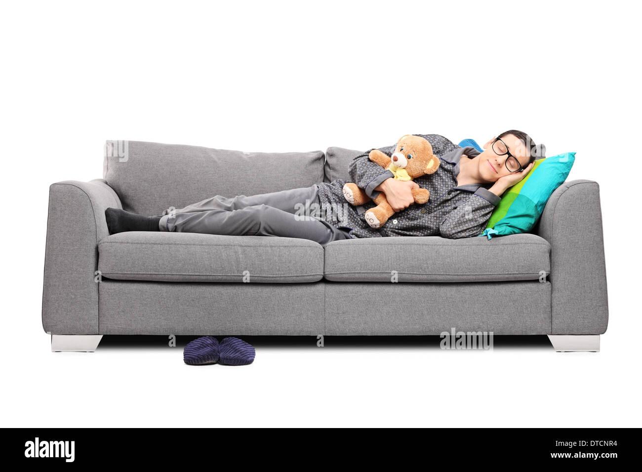 Divano Comodo Per Dormire giovane uomo in pigiama che dorme sul divano con teddy bear