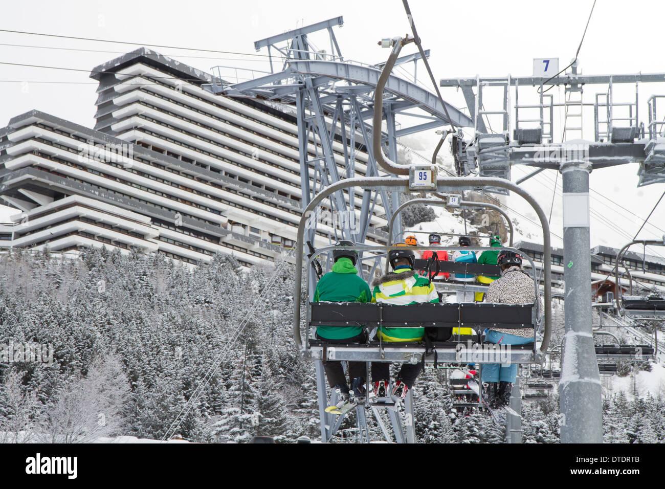 Gli sciatori in una seggiovia in Les Menuires, Trois Vallees, Francia Immagini Stock