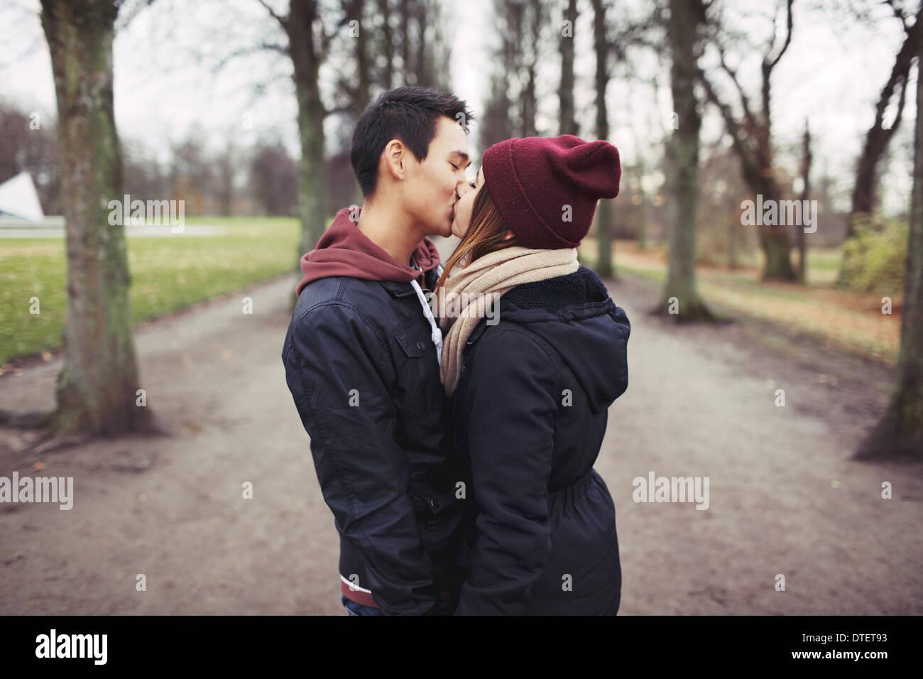 Amorevole coppia giovane kissing all'aperto nel parco. Razza mista l uomo e la donna. Amore adolescenziale. Immagini Stock