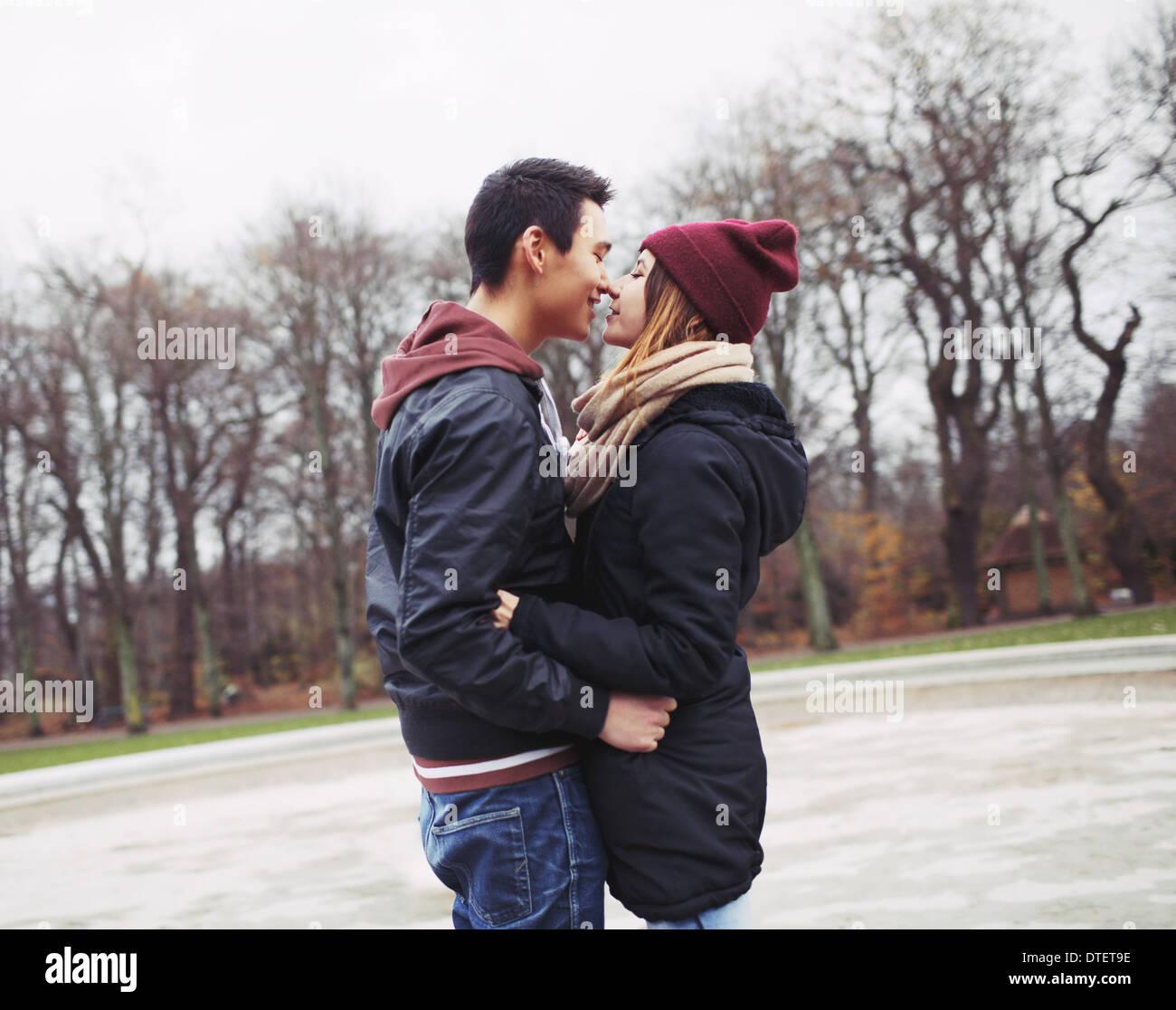 Razza mista teenage matura circa avere un appassionato bacio nel parco. Bel giovane e bella giovane donna in abiti caldi. Immagini Stock