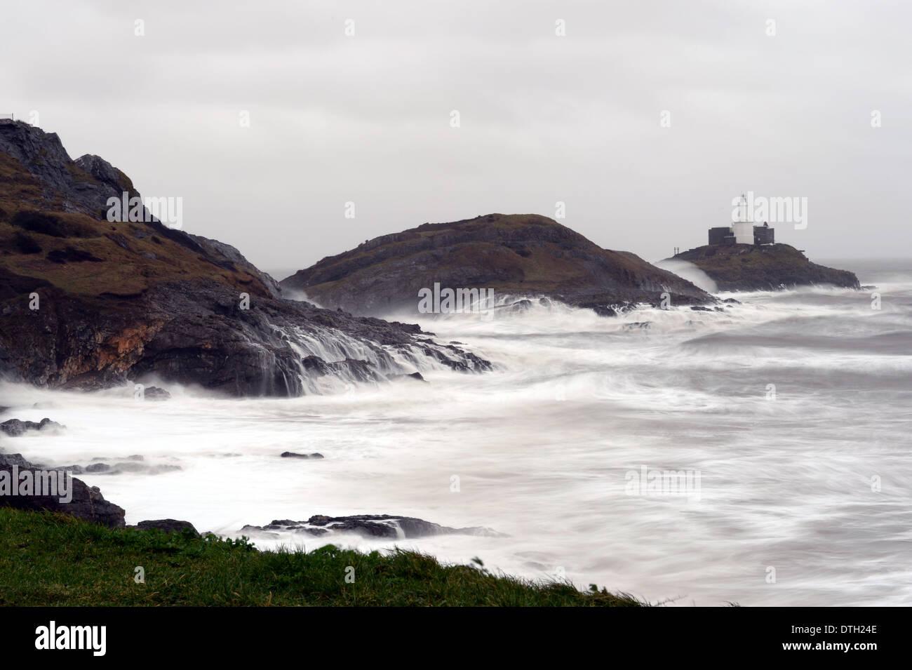 Tempesta innalzamenti di surf sulle isole di Mumbles testa ad alta marea con Mumbles Lighthouse, bracciale Bay, Foto Stock