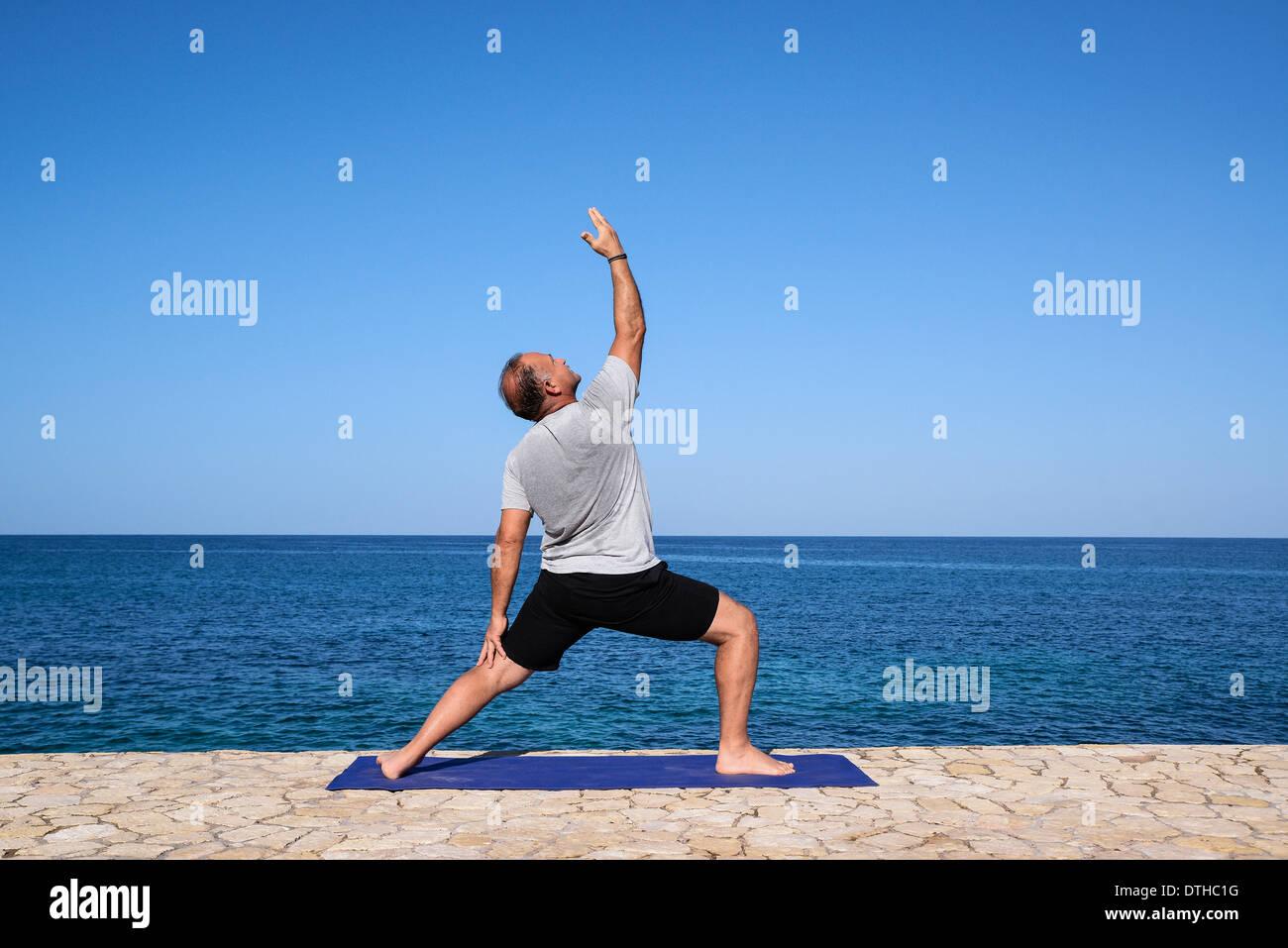 L'uomo pratica yoga meditazione da un oceano waterfront battuta, Negril, Giamaica. Immagini Stock