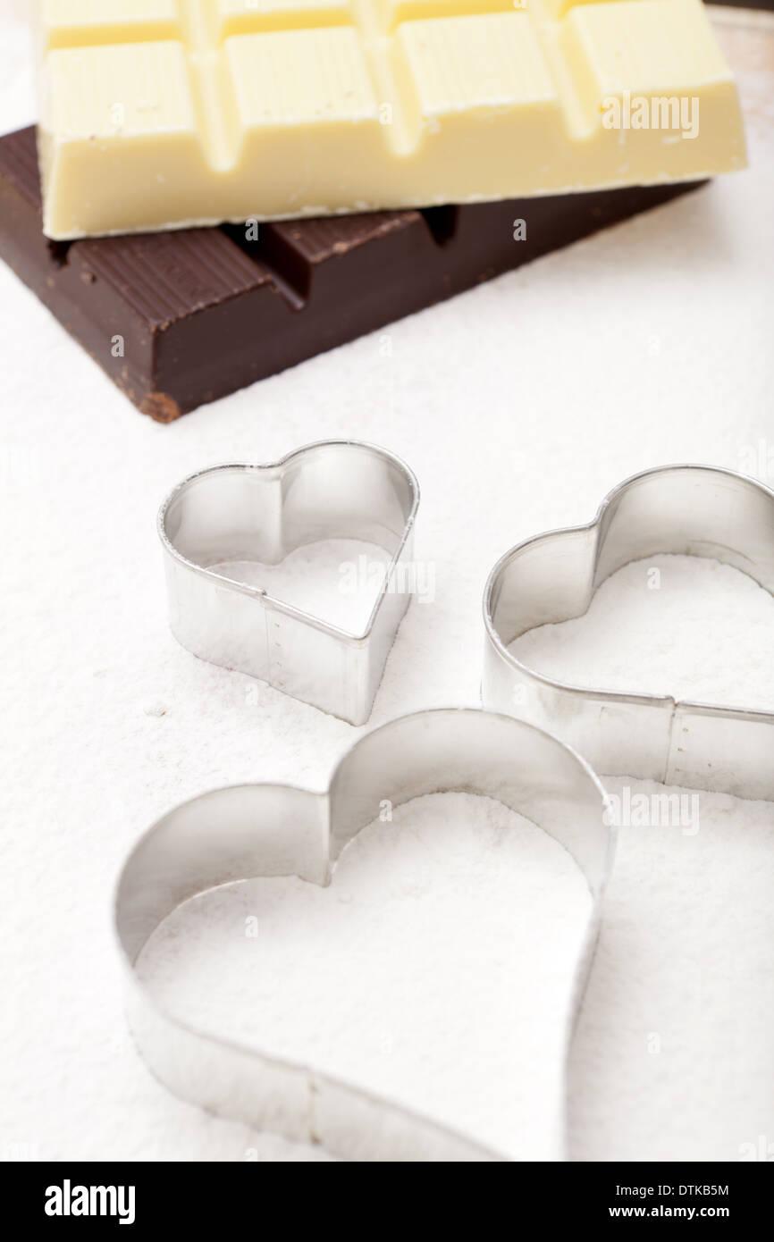 Cookie cutter a forma di cuore sulla farina sullo sfondo bianco e cioccolato fondente Foto Stock