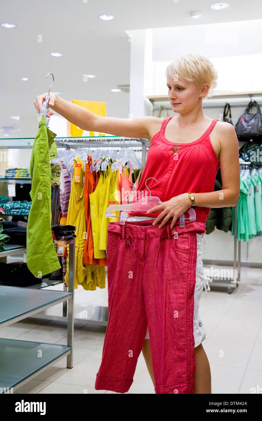 Donna che guarda e confrontare i diversi vestiti in negozio. Moda ... 8250c5ad840