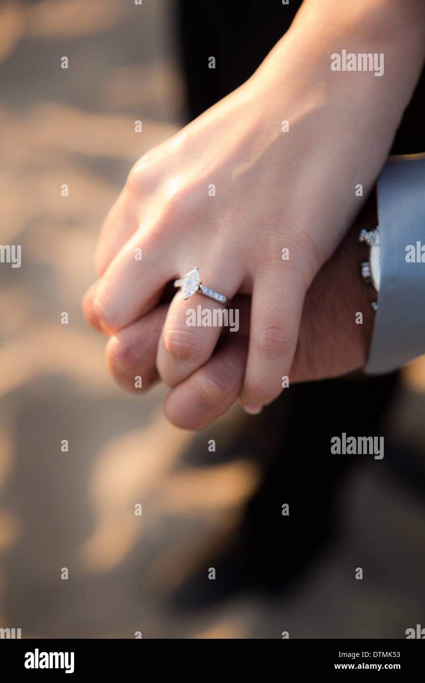 Coppia asiatica in spiaggia a mostrare il loro anello di fidanzamento con diamante e rubare baci e abbracci Immagini Stock