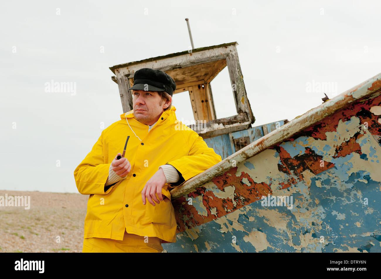 Pescatore in giallo impermeabilizza appoggiata contro una vecchia barca da pesca e fumare una tubazione. Immagini Stock