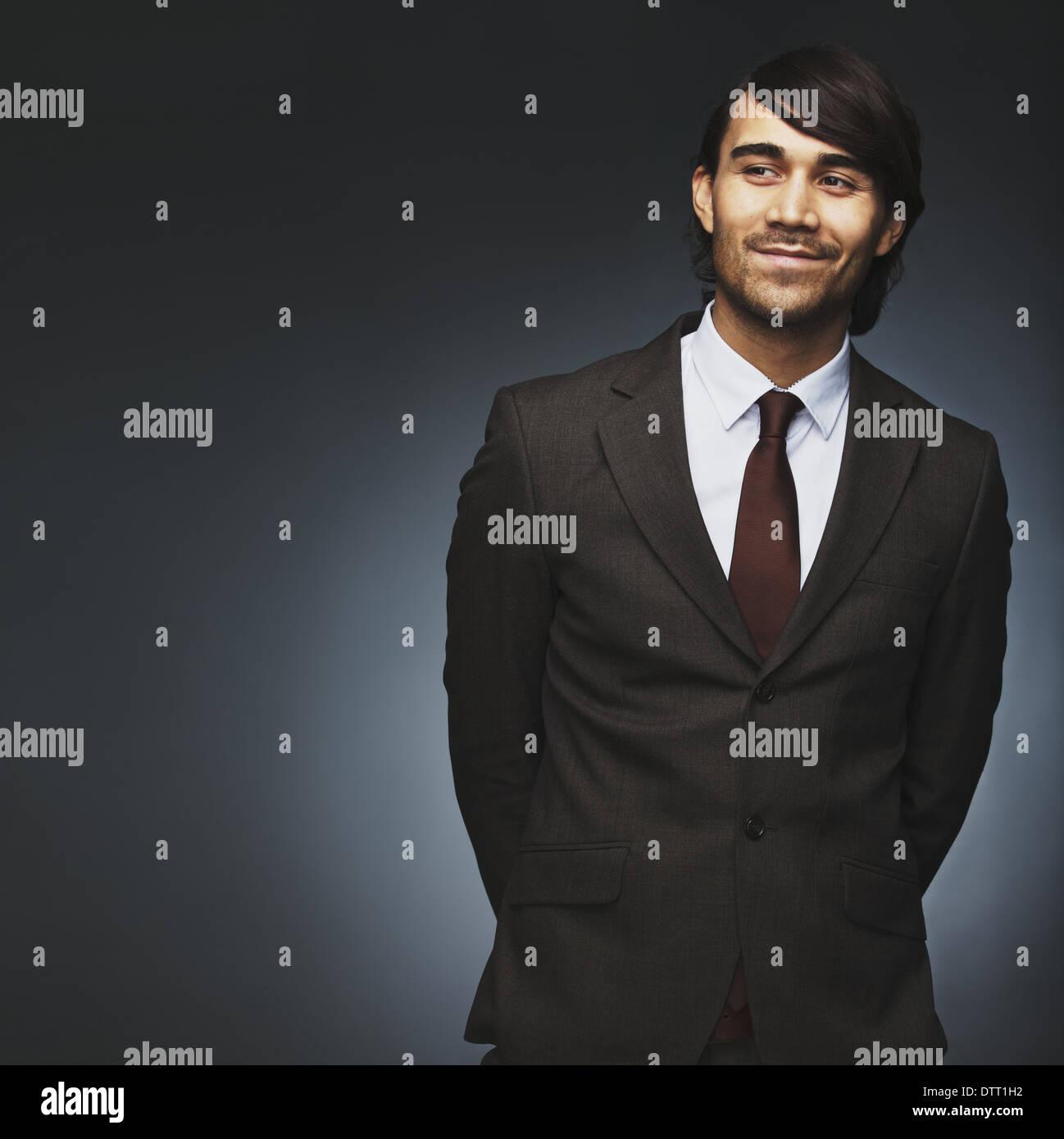 Bel giovane che guarda lontano sorridente su sfondo nero. Modello maschile in business suit guardando copyspace. Immagini Stock