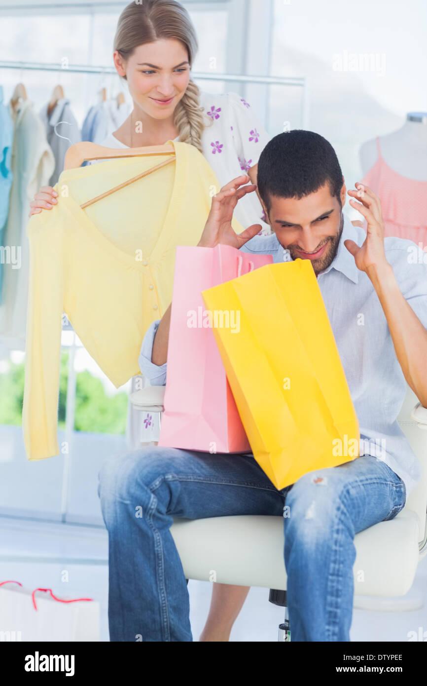 L'uomo arrabbiato mentre la sua ragazza è lo shopping Immagini Stock