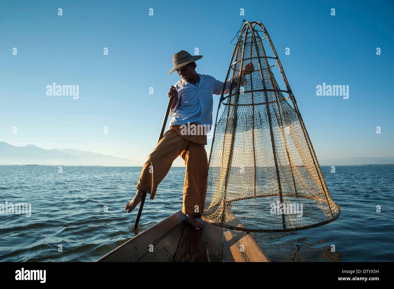 Fisherman, gamba vogatore con un tradizionale cestello sul Canoa Lago Inle, Stato Shan, Myanmar Immagini Stock