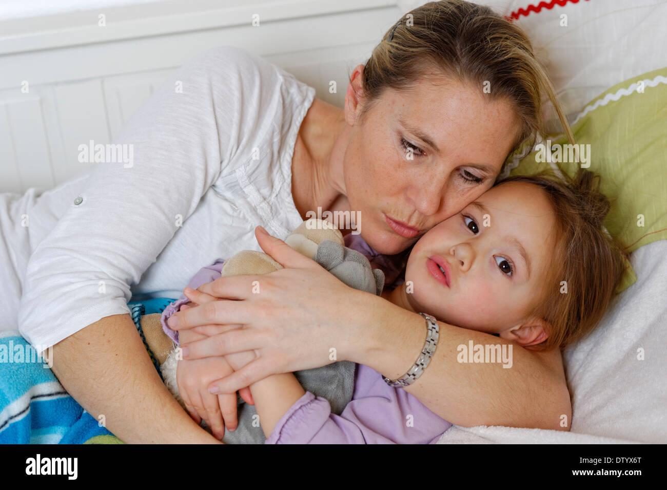 Madre e figlia coccole a letto, avvolgente Immagini Stock