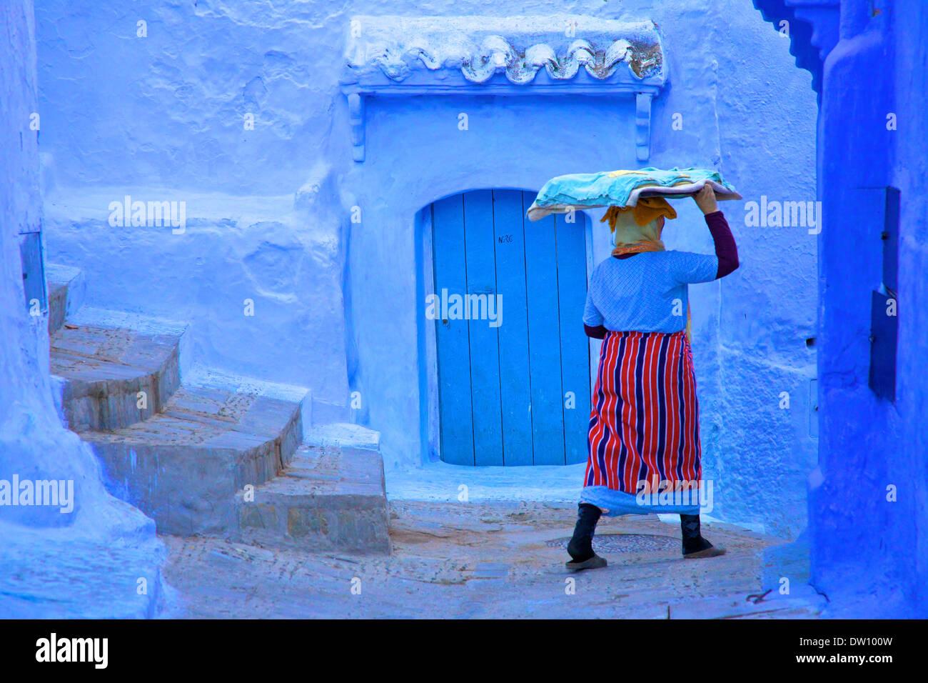 Donna in abiti tradizionali portando un vassoio di pasta di pane, Chefchaouen, Marocco, Africa del Nord Foto Stock