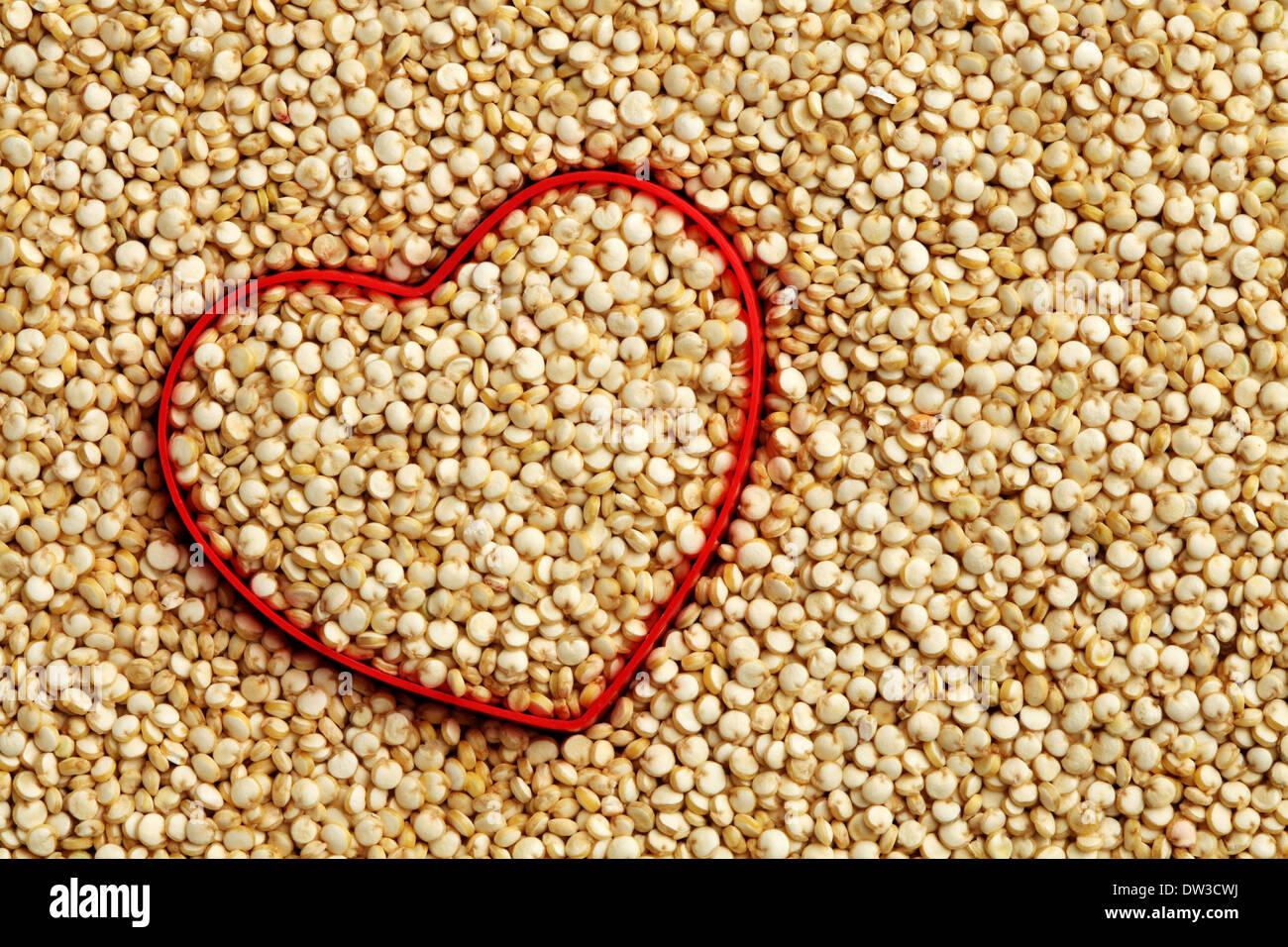 Cuore rosso forma a crudo su sfondo di quinoa Immagini Stock