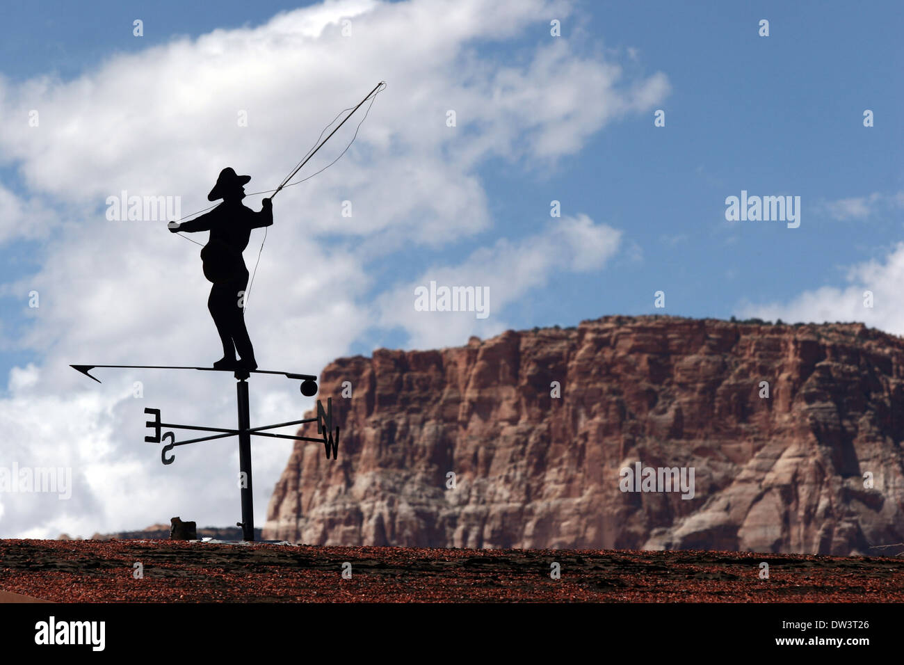 Segnale di vento pescatore sul tetto con rocce e cielo sullo sfondo Immagini Stock