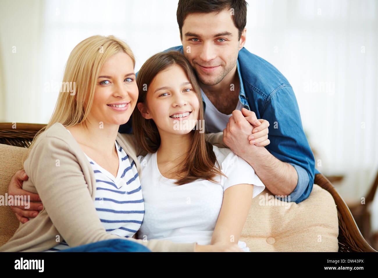 Ritratto di famiglia felice di tre guardando la telecamera con un sorriso Foto Stock