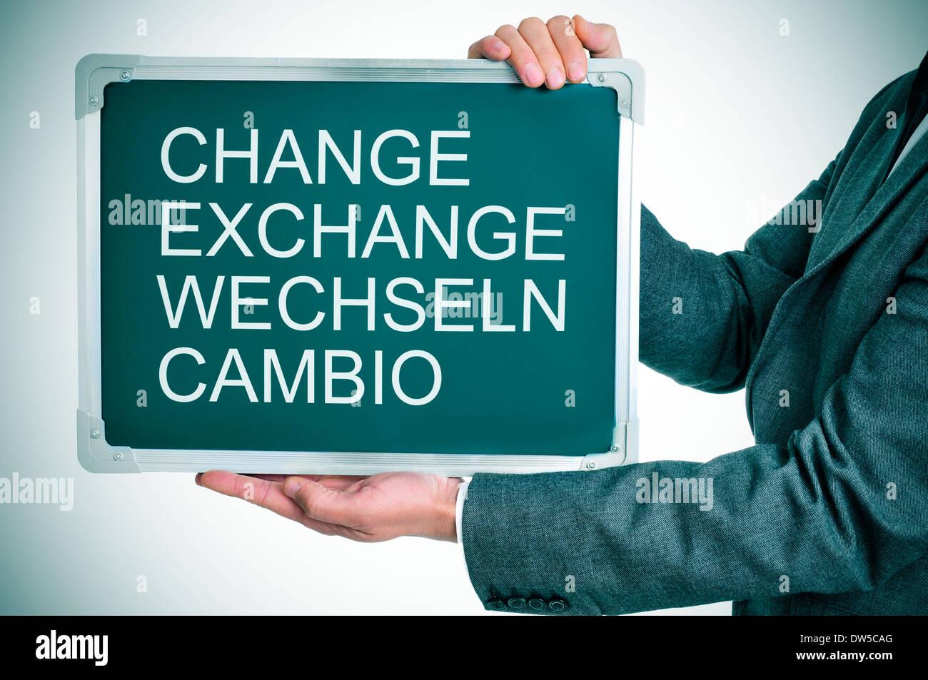 L uomo indossa una tuta in possesso di una lavagna con le parole cambiano, exchange, wechseln, cambio scritto in Foto Stock