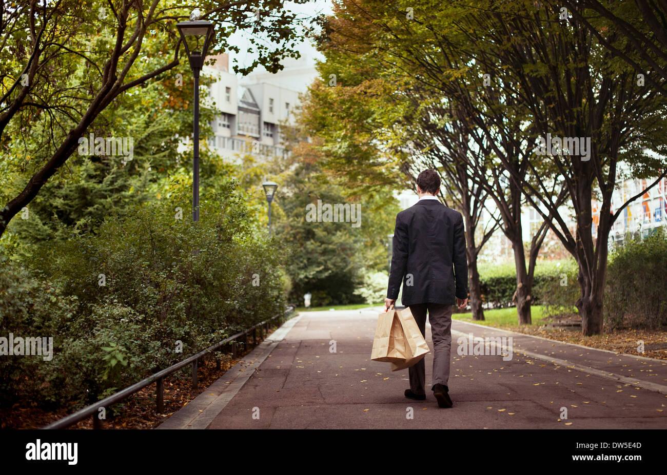 Solitudine, lonely man con borse per lo shopping a piedi dopo il lavoro Immagini Stock