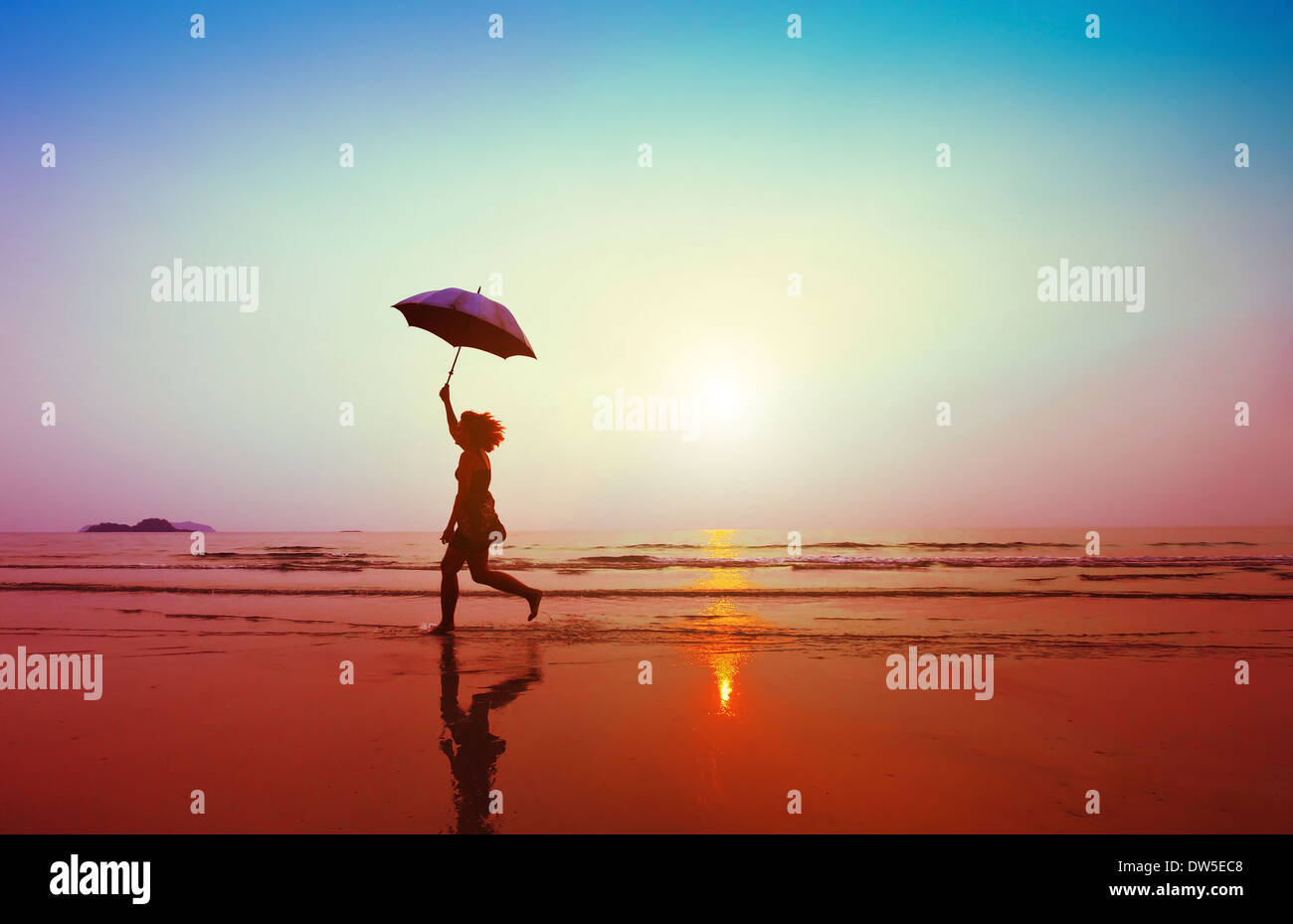 Donna felice jumping con ombrellone in spiaggia Immagini Stock