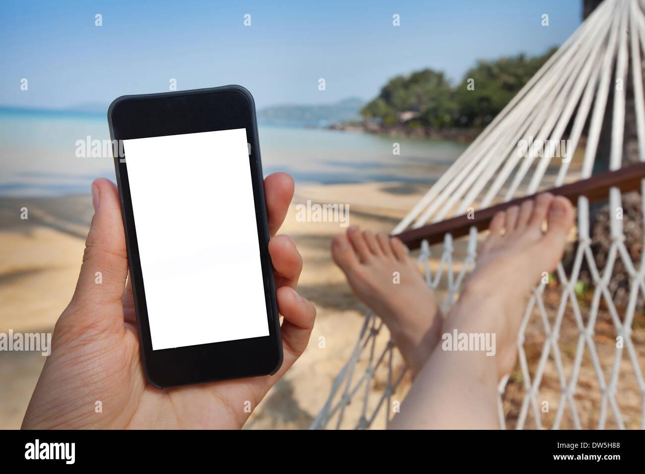 Smartphone in mano in spiaggia amaca Immagini Stock