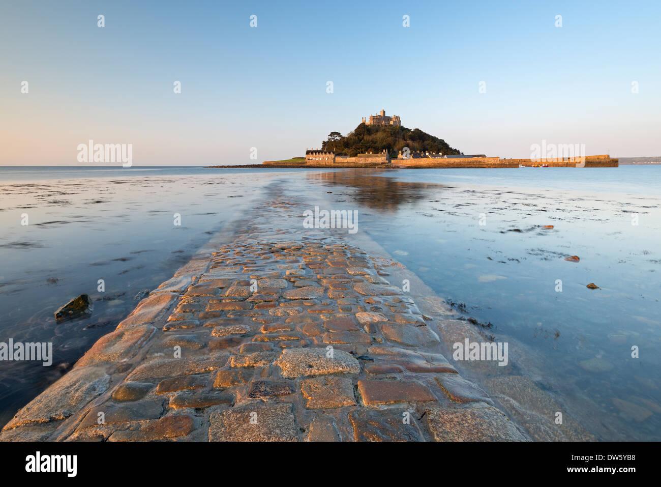 Il selciato in pietra che portano a St Michaels Mount in inizio di mattina di sole, Marazion, Cornwall, Inghilterra. Molla (maggio) 2013. Immagini Stock