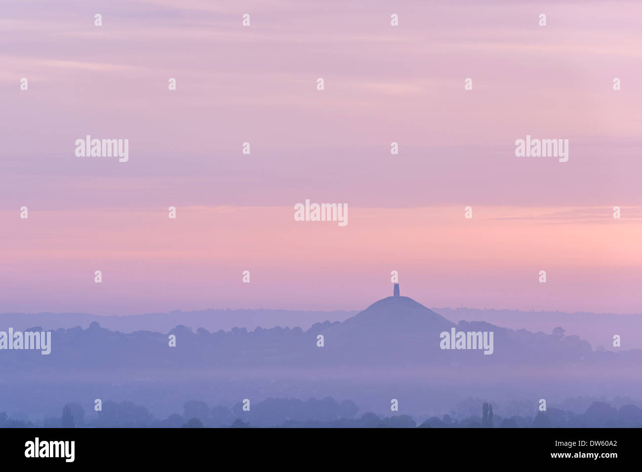 Glastonbury Tor rising circondato da nebbia all'alba, Somerset, Inghilterra. Estate (Agosto) 2013. Immagini Stock
