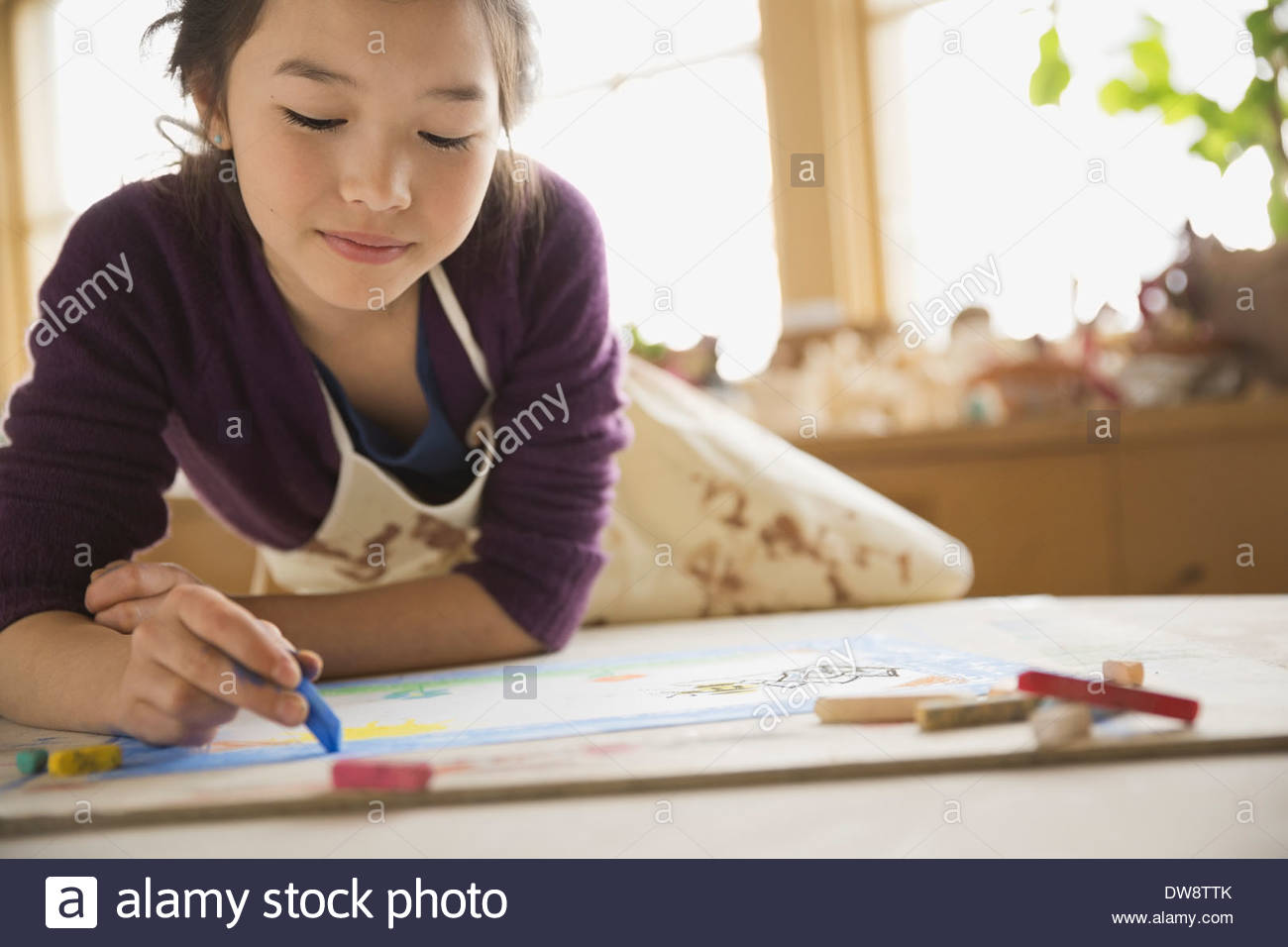 Ragazza di disegno con colori pastello in classe d'arte Immagini Stock