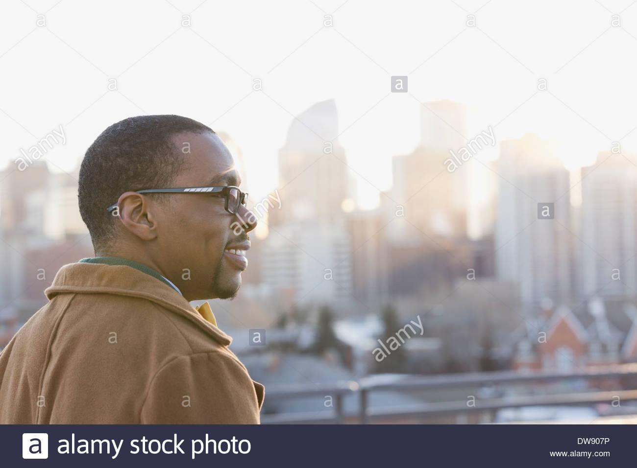 Uomo sorridente guardando cityscape Immagini Stock
