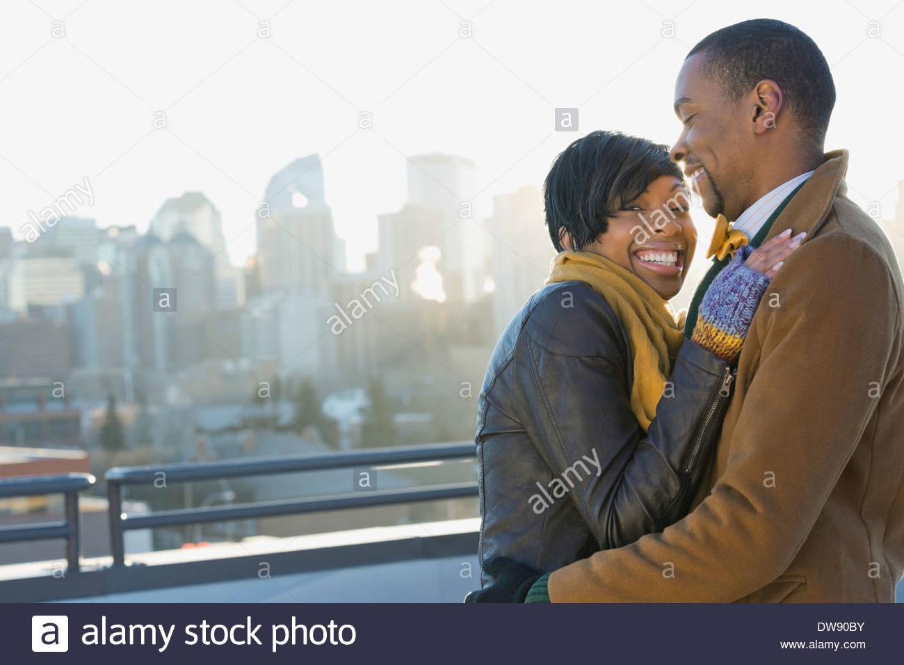 Coppia sorridente in piedi all'aperto contro cityscape Immagini Stock