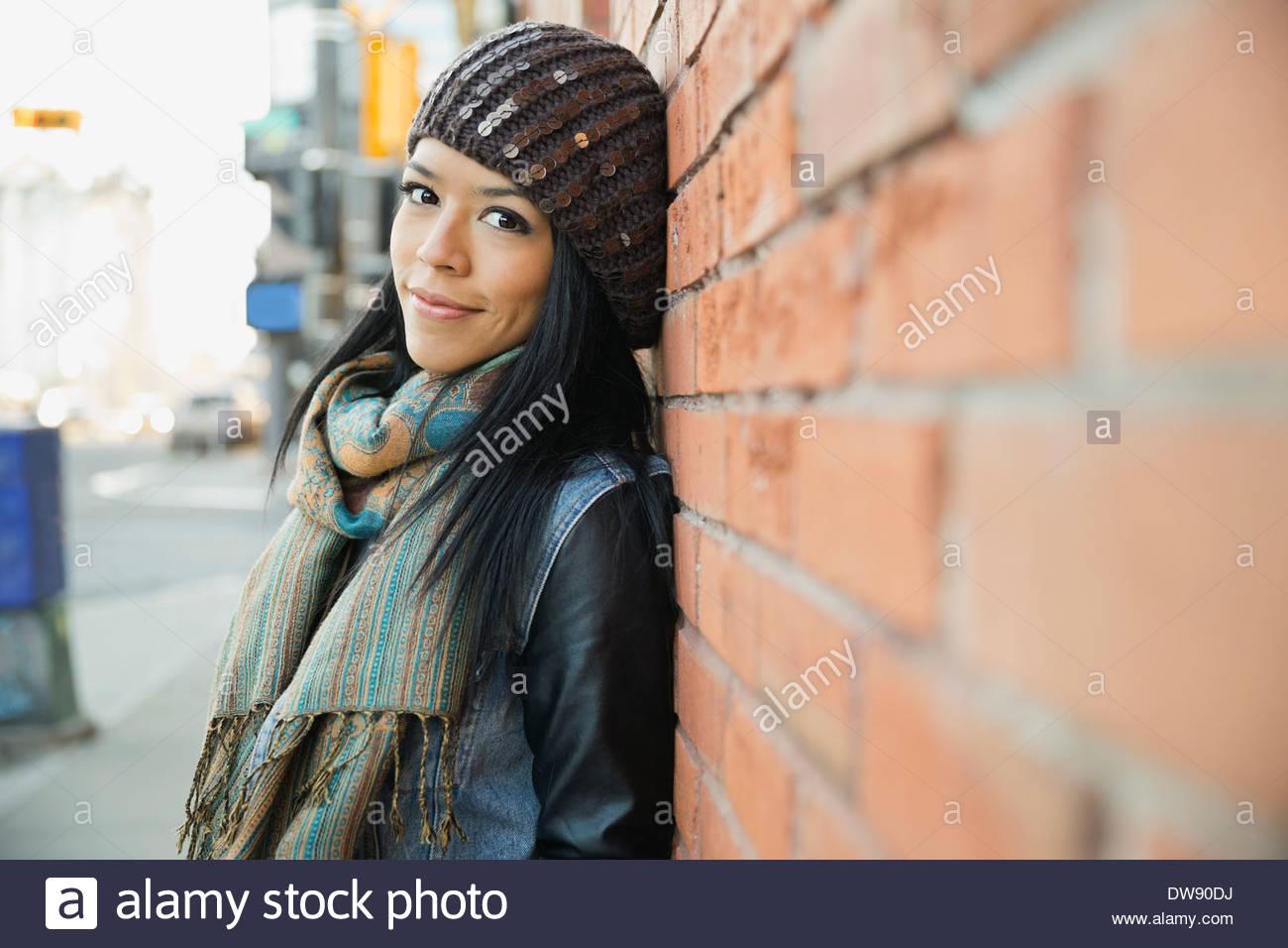 Ritratto di donna appoggiata contro un muro di mattoni Immagini Stock