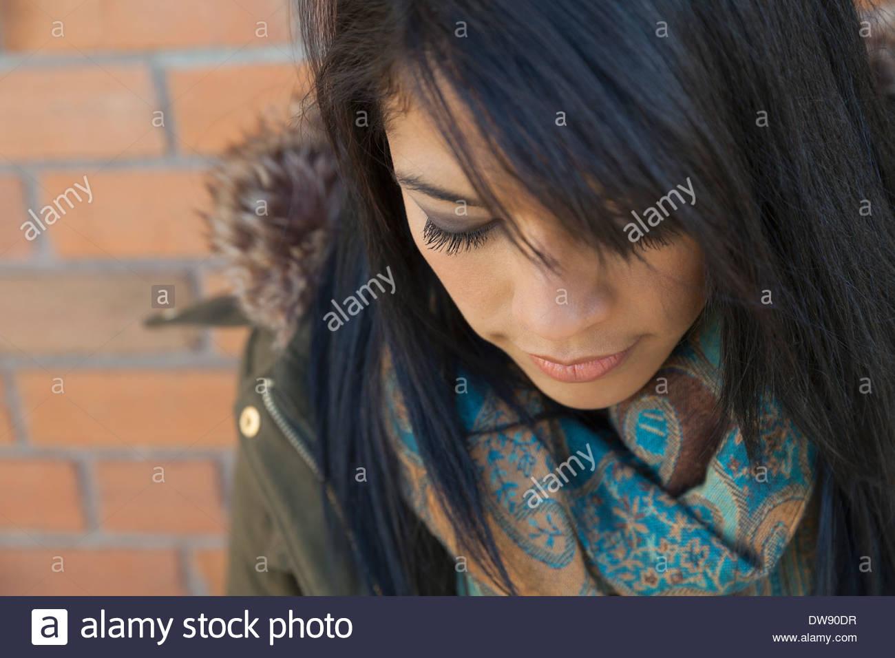 Close-up di donna che guarda verso il basso contro la parete in mattoni Immagini Stock