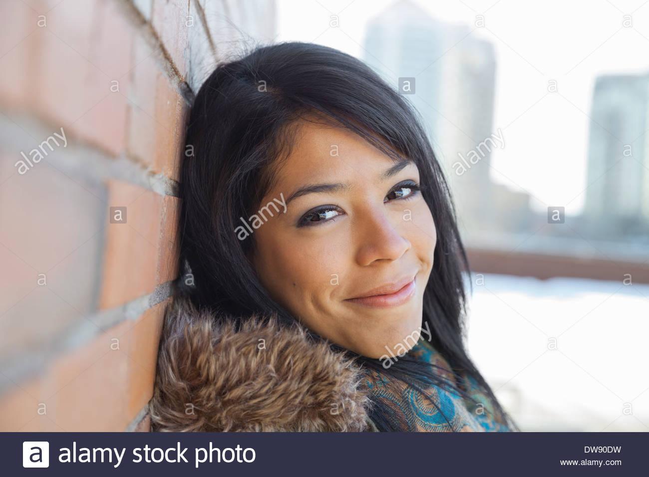 Ritratto di donna sorridente appoggiato contro un muro di mattoni Immagini Stock