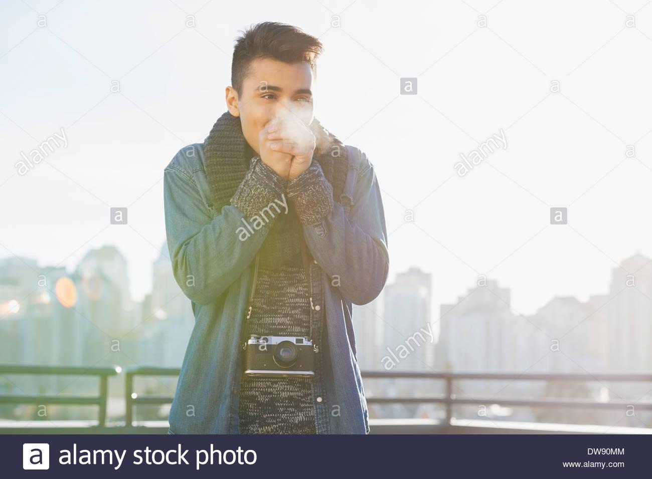 Uomo in piedi all'aperto mani di riscaldamento in inverno Immagini Stock