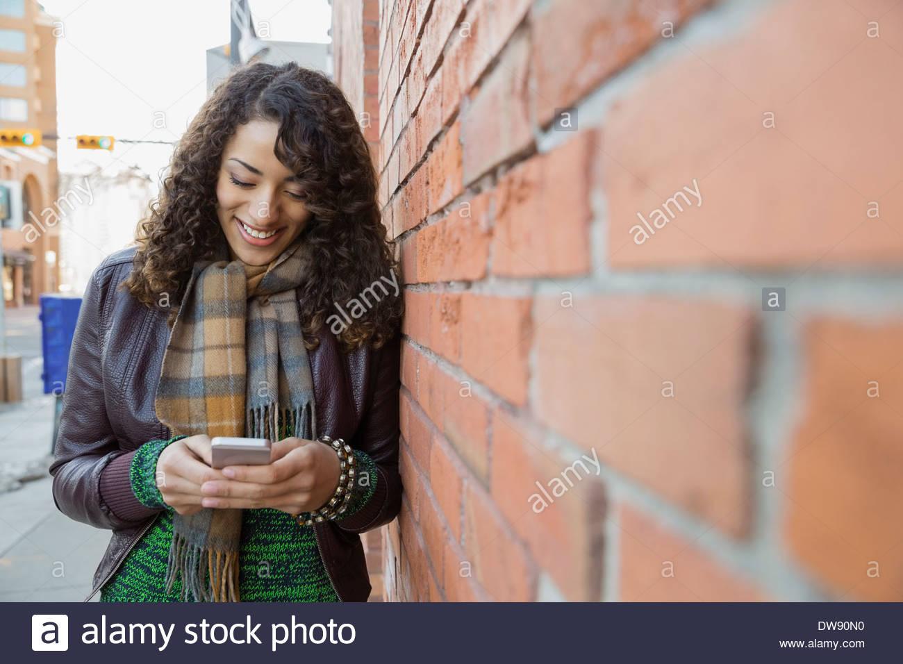 Donna sorridente con smart phone dal muro di mattoni Immagini Stock