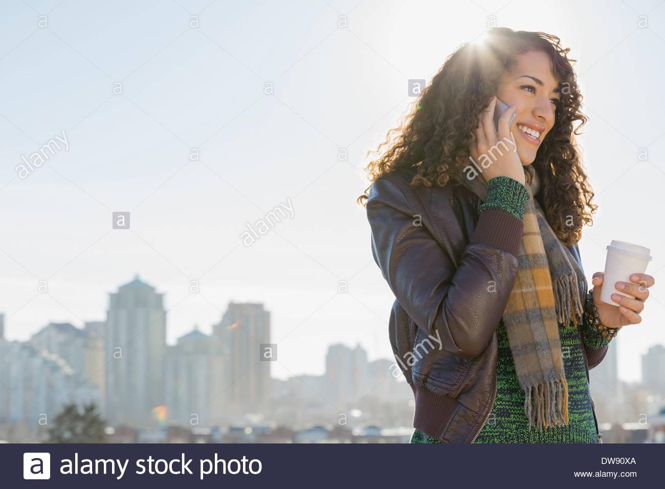 Donna sorridente rispondendo alle smart phone contro cityscape Immagini Stock