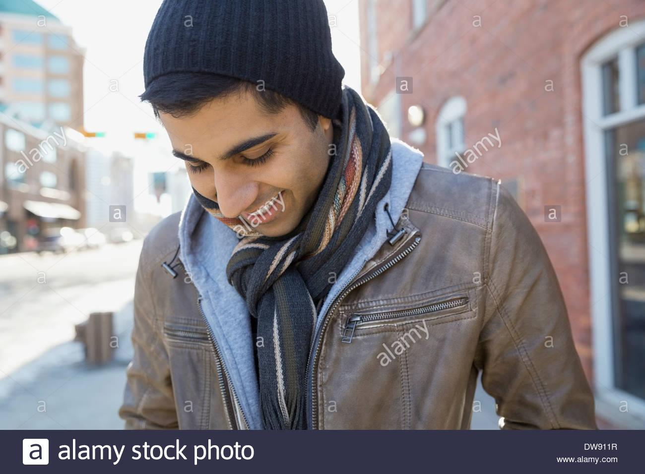 Uomo sorridente in piedi all'esterno guardando verso il basso Immagini Stock