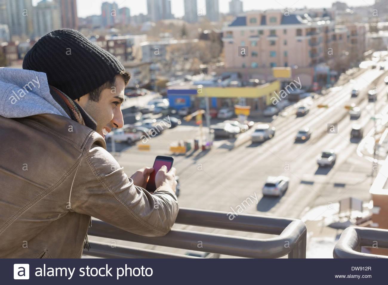 Uomo con smart phone appoggiata sulla ringhiera del patio Immagini Stock