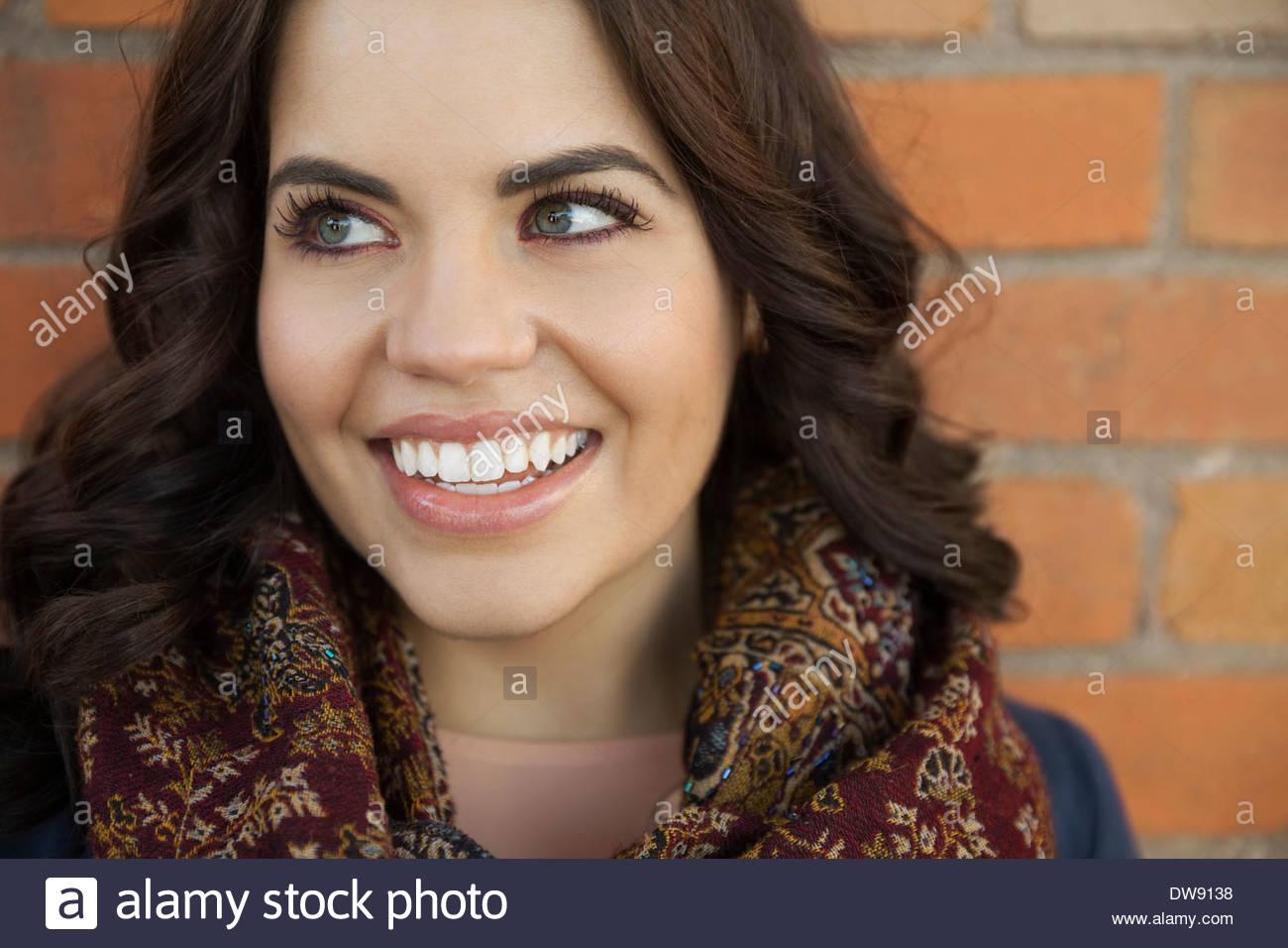 Bella donna sorridente contro un muro di mattoni Immagini Stock