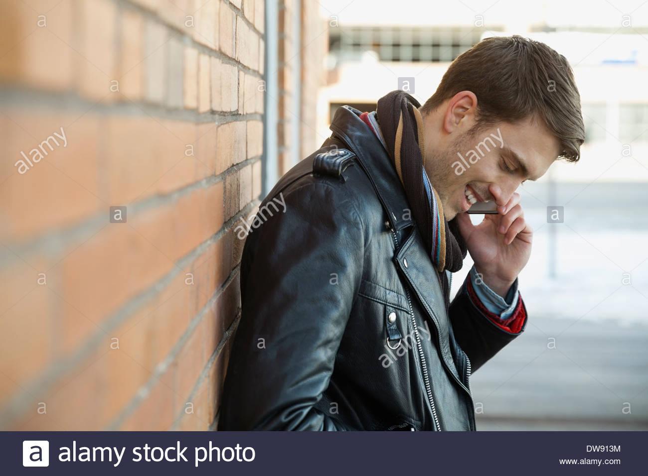 Uomo sorridente rispondendo alle smart phone all'aperto Immagini Stock
