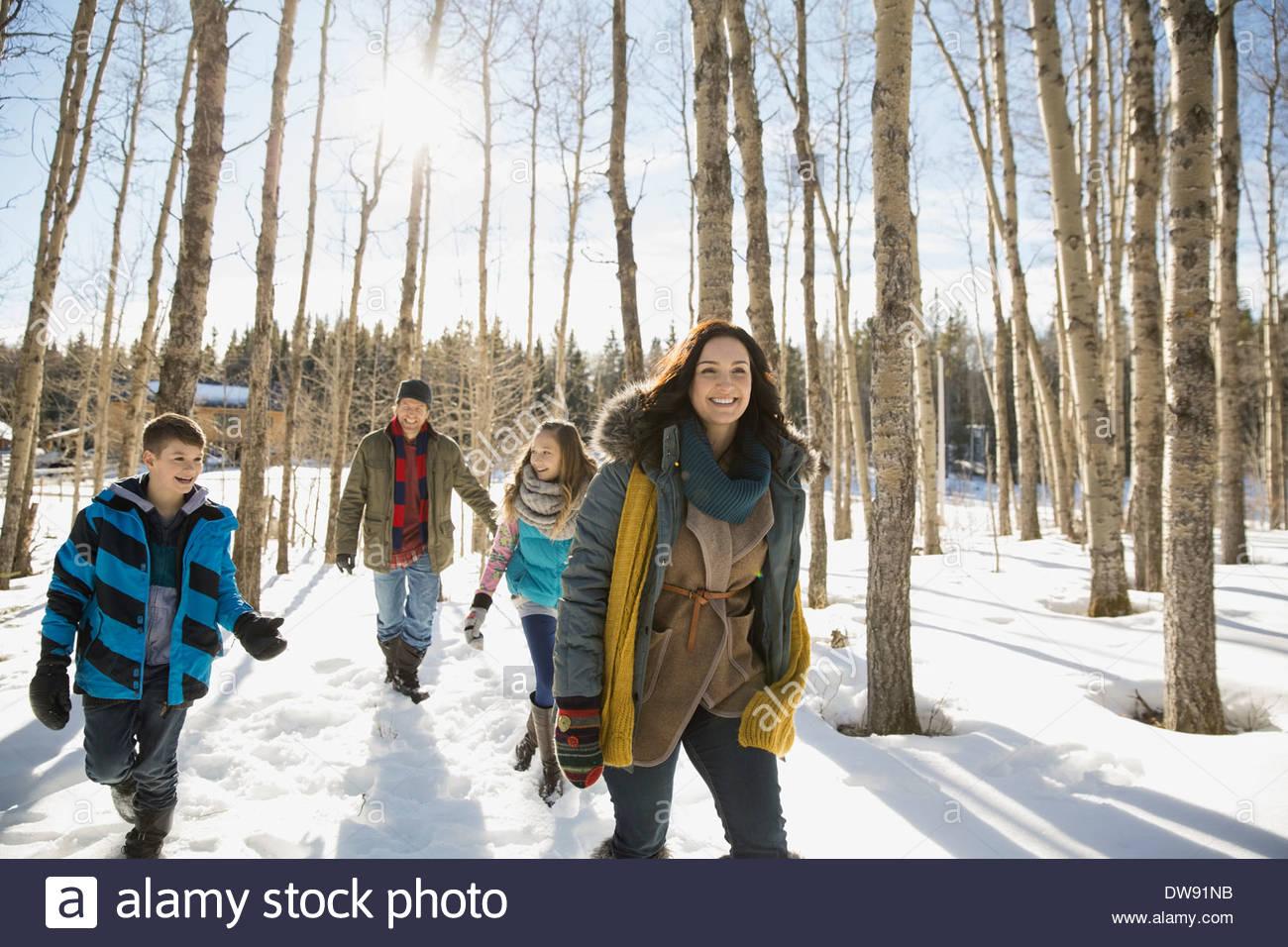 Famiglia camminare attraverso la foresta di inverno Immagini Stock