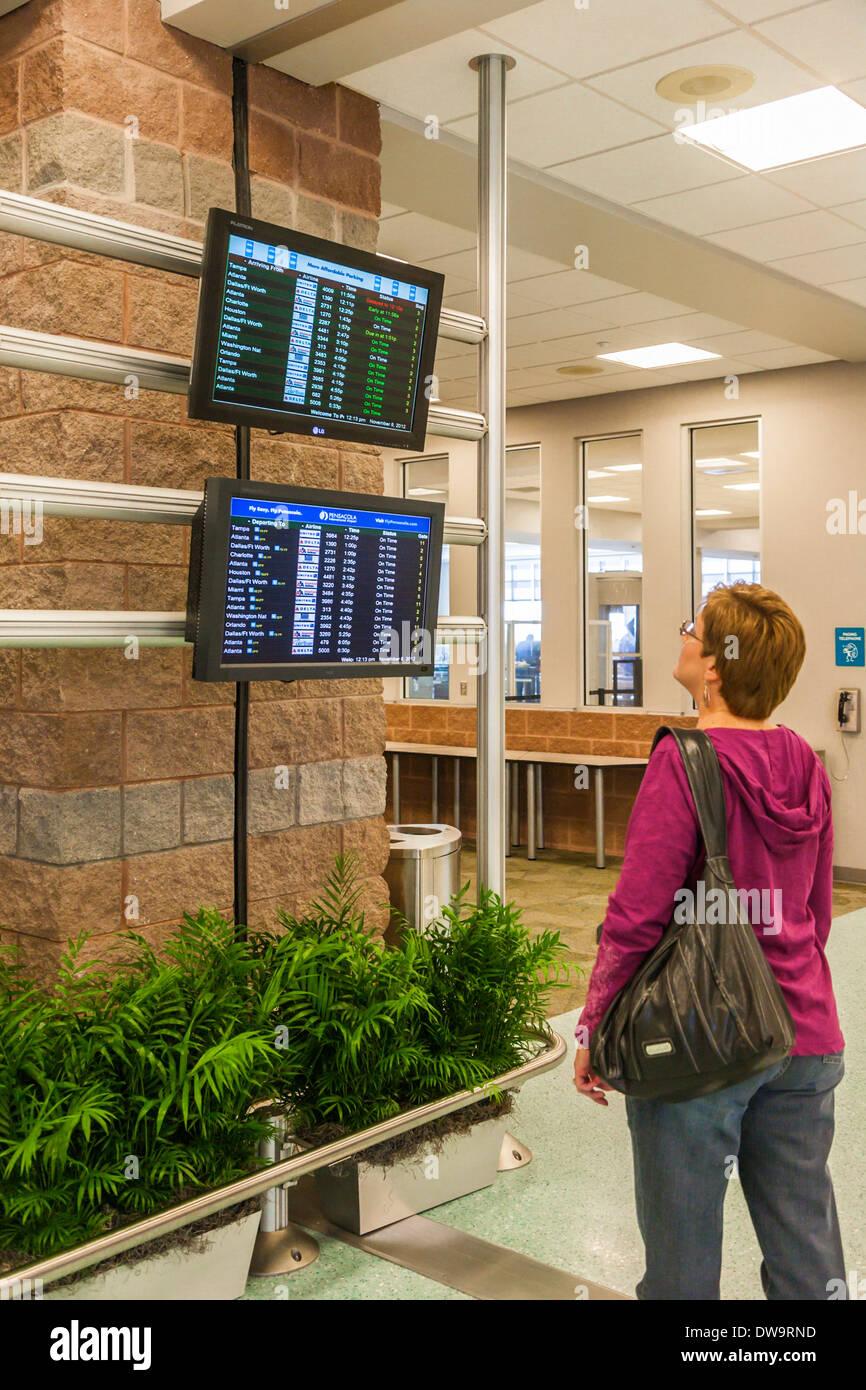 Donna che guarda un arrivo e partenza schermi di Pensacola International Airport in Pensacola, Florida Immagini Stock