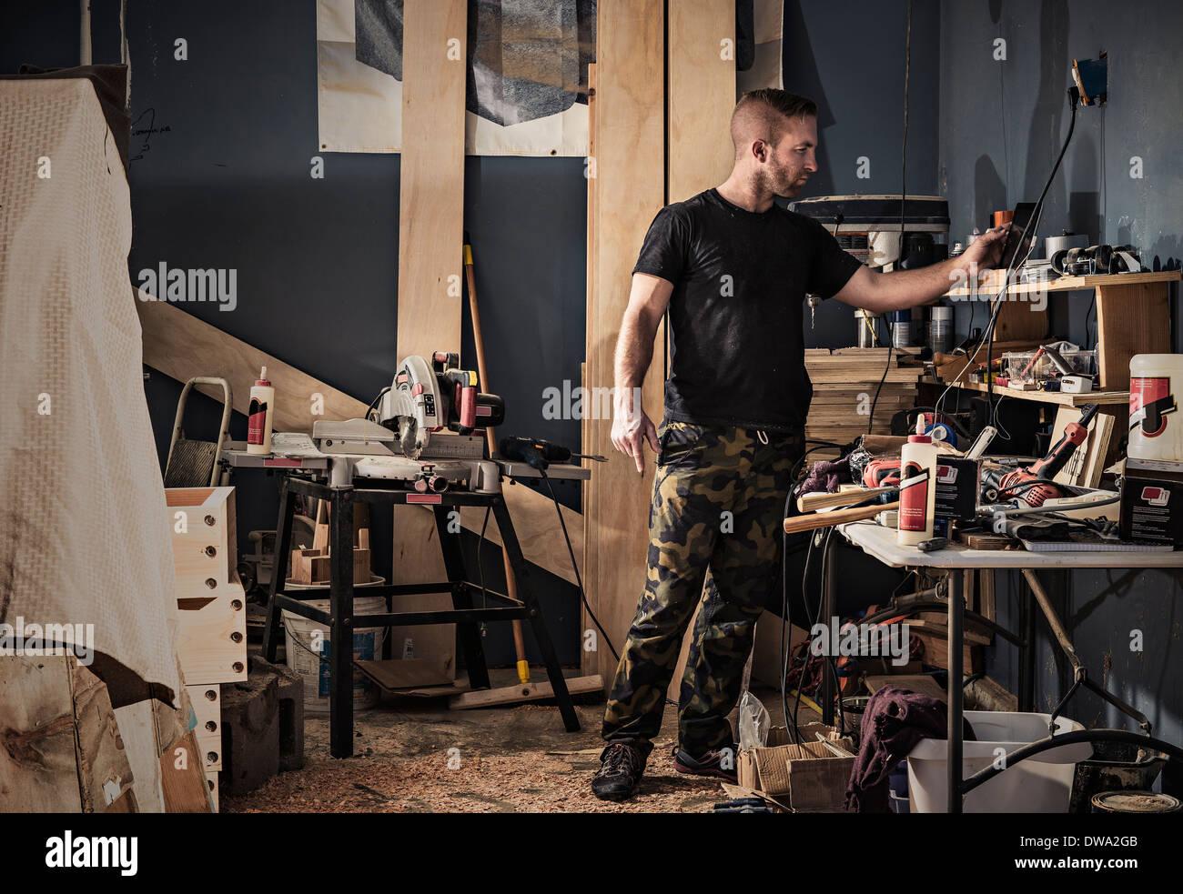 Falegname maschio alla ricerca di scaffali in officina Immagini Stock