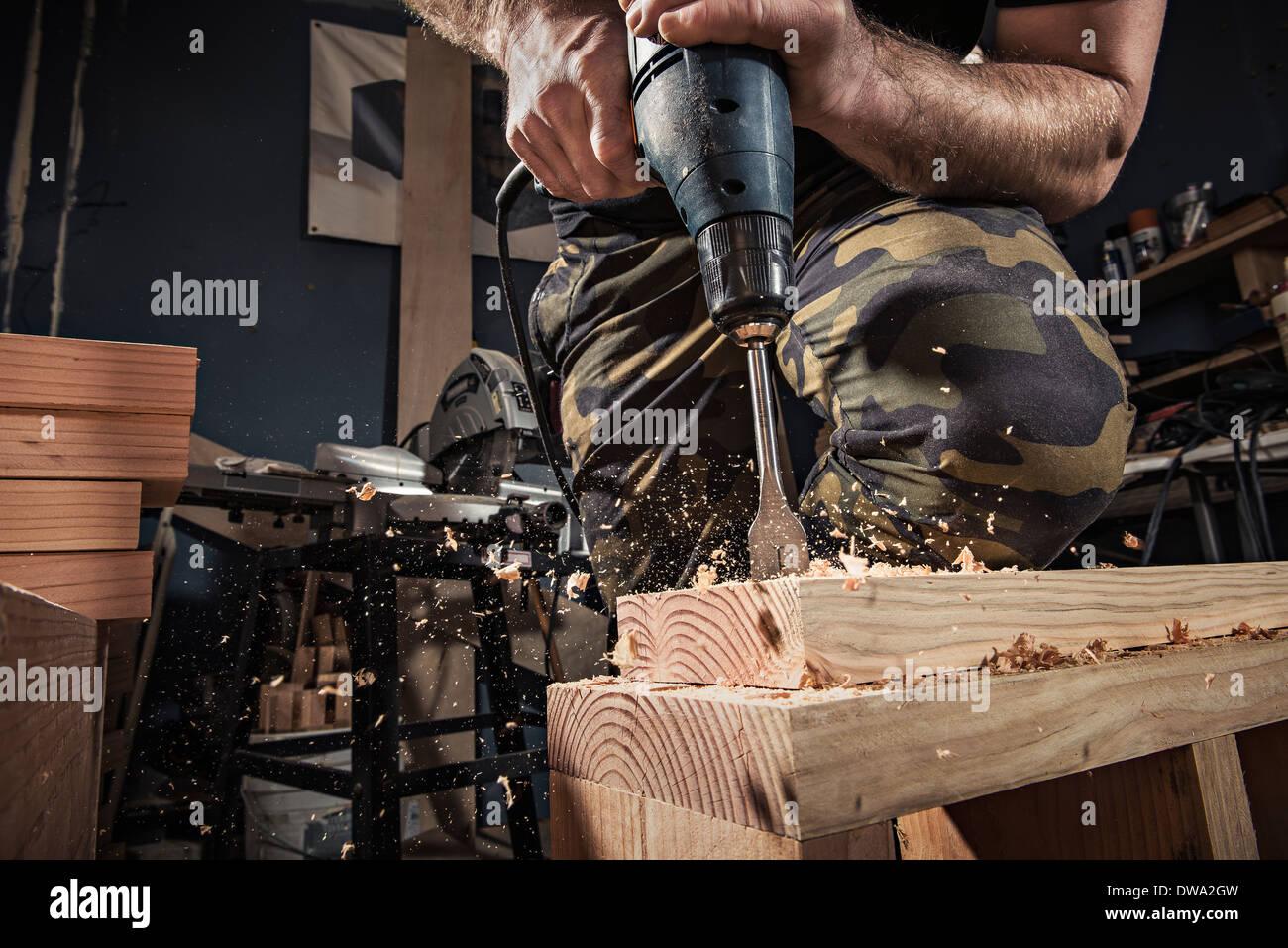 Chiusura del maschio di perforazione carpenter tavolato in legno in laboratorio Immagini Stock