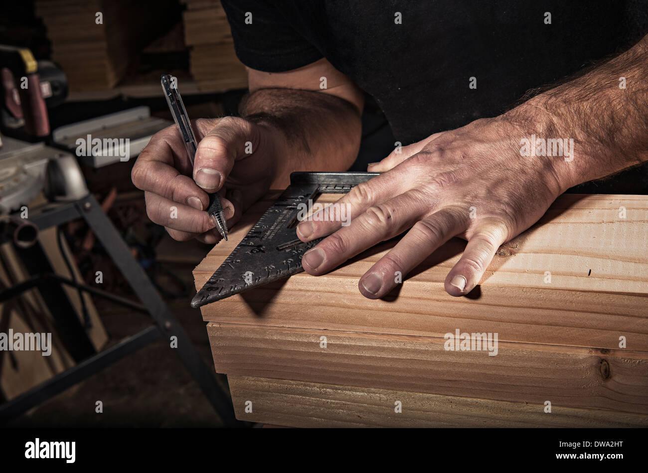 Chiusura del falegname maschio utilizzando set square in officina Immagini Stock