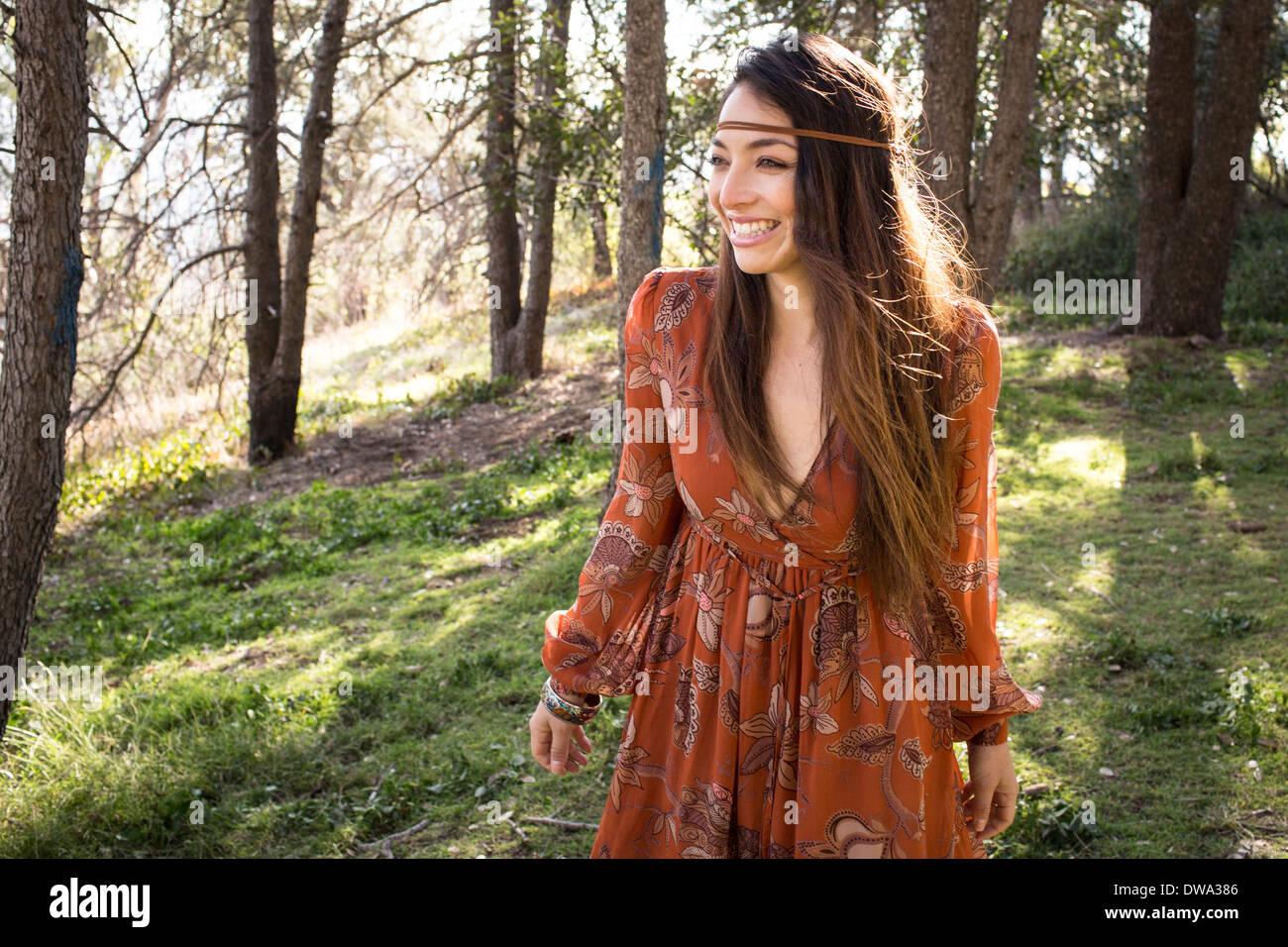Ritratto di giovane donna che indossa abiti in foresta, sorridente Immagini Stock