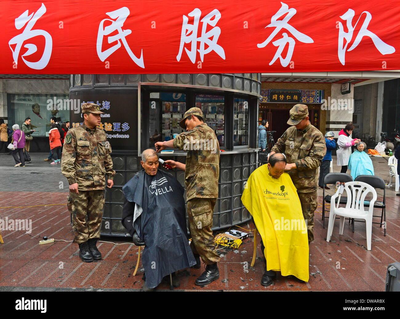 """Shanghai, soldato cinese negli anni sessanta. Il 15 agosto, 1962. Soldati offerta free haircut servizio ai cittadini a Shanghai in Cina orientale, 5 marzo 2014, in occasione della """"Lei Feng's Day"""", che cade il 5 marzo di ogni anno. Lei, un giovane soldato cinese negli anni sessanta, è noto per aver dedicato quasi tutto il suo tempo di ricambio e denaro per aiutare disinteressatamente i bisognosi. Egli è morto dopo essere stato colpito da una caduta di pole mentre aiutando un compagno soldato dirigere un carrello su 15 Agosto 1962. Credito: Guo Changyao/Xinhua/Alamy Live News Immagini Stock"""