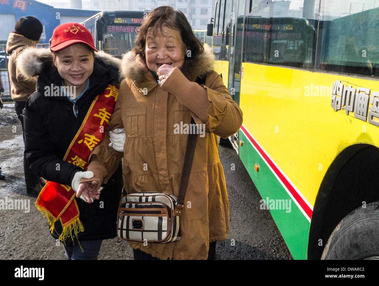 """Urumqi, soldato cinese negli anni sessanta. Il 15 agosto, 1962. Un volontario aiuta una donna anziana su un autobus in Urumqi, capitale del nord-ovest della Cina di Xinjiang Uygur Regione autonoma, 5 marzo 2014, in occasione della """"Lei Feng's Day"""", che cade il 5 marzo di ogni anno. Lei, un giovane soldato cinese negli anni sessanta, è noto per aver dedicato quasi tutto il suo tempo di ricambio e denaro per aiutare disinteressatamente i bisognosi. Egli è morto dopo essere stato colpito da una caduta di pole mentre aiutando un compagno soldato dirigere un carrello su 15 Agosto 1962. Credito: Wang Fei/Xinhua/Alamy Live News Immagini Stock"""
