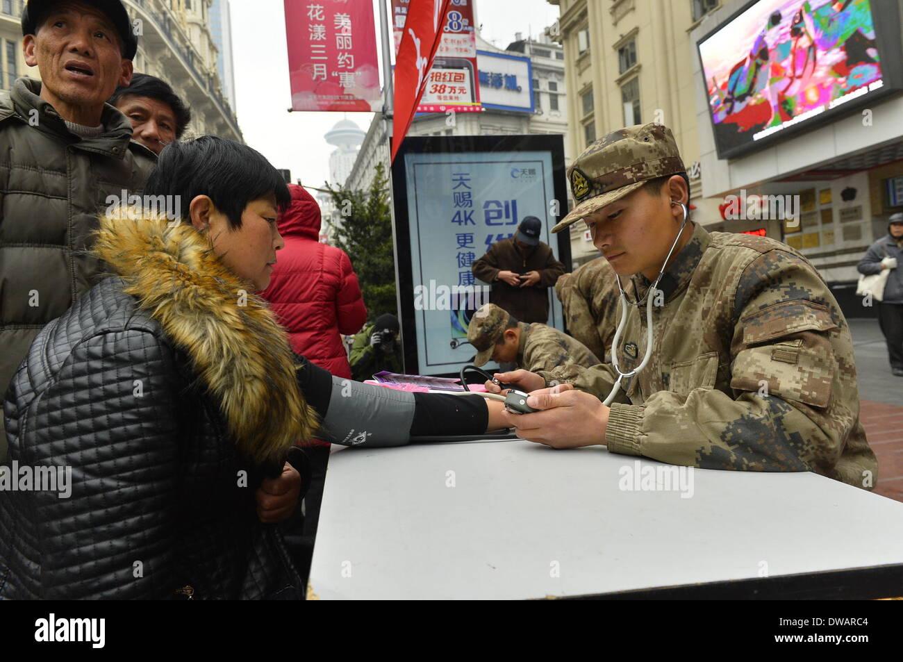 """Shanghai, soldato cinese negli anni sessanta. Il 15 agosto, 1962. Un volontario medico militare controlli di una donna e la pressione del sangue a Shanghai in Cina orientale, 5 marzo 2014, in occasione della """"Lei Feng's Day"""", che cade il 5 marzo di ogni anno. Lei, un giovane soldato cinese negli anni sessanta, è noto per aver dedicato quasi tutto il suo tempo di ricambio e denaro per aiutare disinteressatamente i bisognosi. Egli è morto dopo essere stato colpito da una caduta di pole mentre aiutando un compagno soldato dirigere un carrello su 15 Agosto 1962. Credito: Guo Changyao/Xinhua/Alamy Live News Immagini Stock"""
