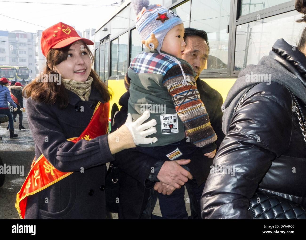 """Urumqi, soldato cinese negli anni sessanta. Il 15 agosto, 1962. Un volontario che aiuta un uomo vecchio e un ragazzo su un autobus in Urumqi, capitale del nord-ovest della Cina di Xinjiang Uygur Regione autonoma, 5 marzo 2014, in occasione della """"Lei Feng's Day"""", che cade il 5 marzo di ogni anno. Lei, un giovane soldato cinese negli anni sessanta, è noto per aver dedicato quasi tutto il suo tempo di ricambio e denaro per aiutare disinteressatamente i bisognosi. Egli è morto dopo essere stato colpito da una caduta di pole mentre aiutando un compagno soldato dirigere un carrello su 15 Agosto 1962. Credito: Wang Fei/Xinhua/Alamy Live News Immagini Stock"""