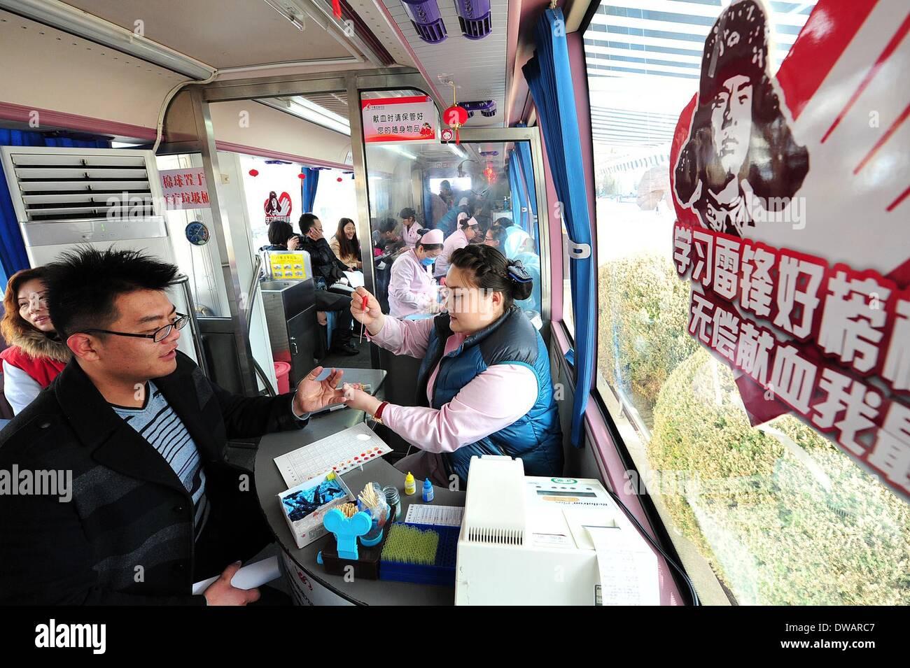 """Yinchuan, soldato cinese negli anni sessanta. Il 15 agosto, 1962. Un giovane uomo dona il sangue a Yinchuan, capitale del nord-ovest della Cina di Ningxia Hui Regione autonoma, 5 marzo 2014, in occasione della """"Lei Feng's Day"""", che cade il 5 marzo di ogni anno. Lei, un giovane soldato cinese negli anni sessanta, è noto per aver dedicato quasi tutto il suo tempo di ricambio e denaro per aiutare disinteressatamente i bisognosi. Egli è morto dopo essere stato colpito da una caduta di pole mentre aiutando un compagno soldato dirigere un carrello su 15 Agosto 1962. Credito: Peng Zhaozhi/Xinhua/Alamy Live News Immagini Stock"""
