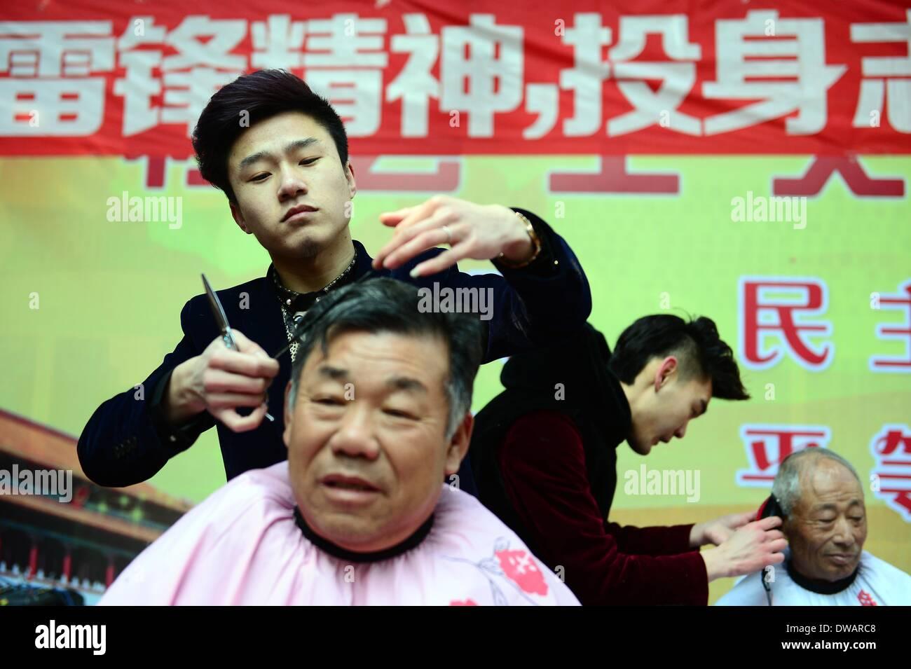 """Weihai, soldato cinese negli anni sessanta. Il 15 agosto, 1962. Un volontario offre gratuitamente il servizio di acconciatura per un uomo vecchio nella città di Weihai, est della Cina di Provincia di Shandong, 5 marzo 2014, in occasione della """"Lei Feng's Day"""", che cade il 5 marzo di ogni anno. Lei, un giovane soldato cinese negli anni sessanta, è noto per aver dedicato quasi tutto il suo tempo di ricambio e denaro per aiutare disinteressatamente i bisognosi. Egli è morto dopo essere stato colpito da una caduta di pole mentre aiutando un compagno soldato dirigere un carrello su 15 Agosto 1962. Credito: Guo Xulei/Xinhua/Alamy Live News Immagini Stock"""